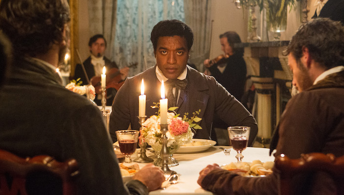 Chiwetel Ejiofor sits at a candlelit table in an opulent dining room in 12 Years a Slave
