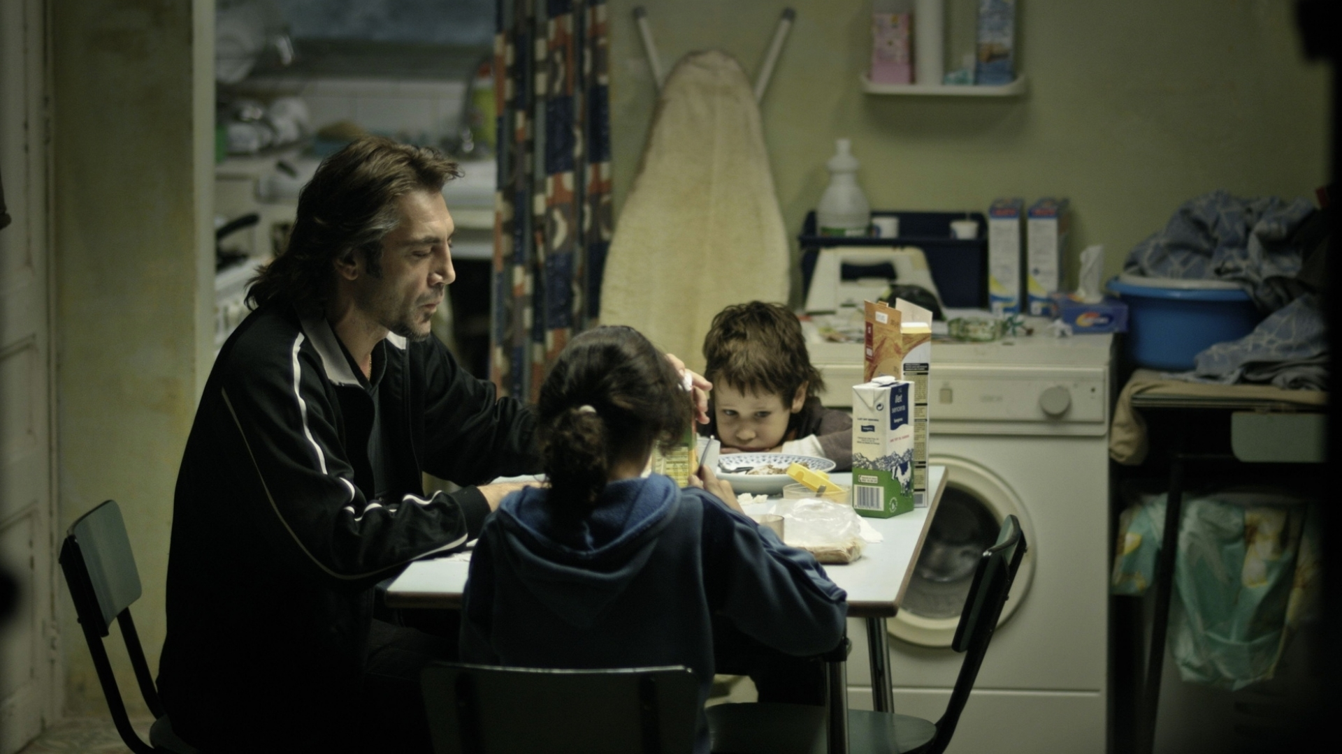 """Javier Bardem and two children, a girl and a boy, in a shot from the film """"Biutiful."""" They are seated around a table eating breakfast in a small, dingy room also used for washing laundry."""