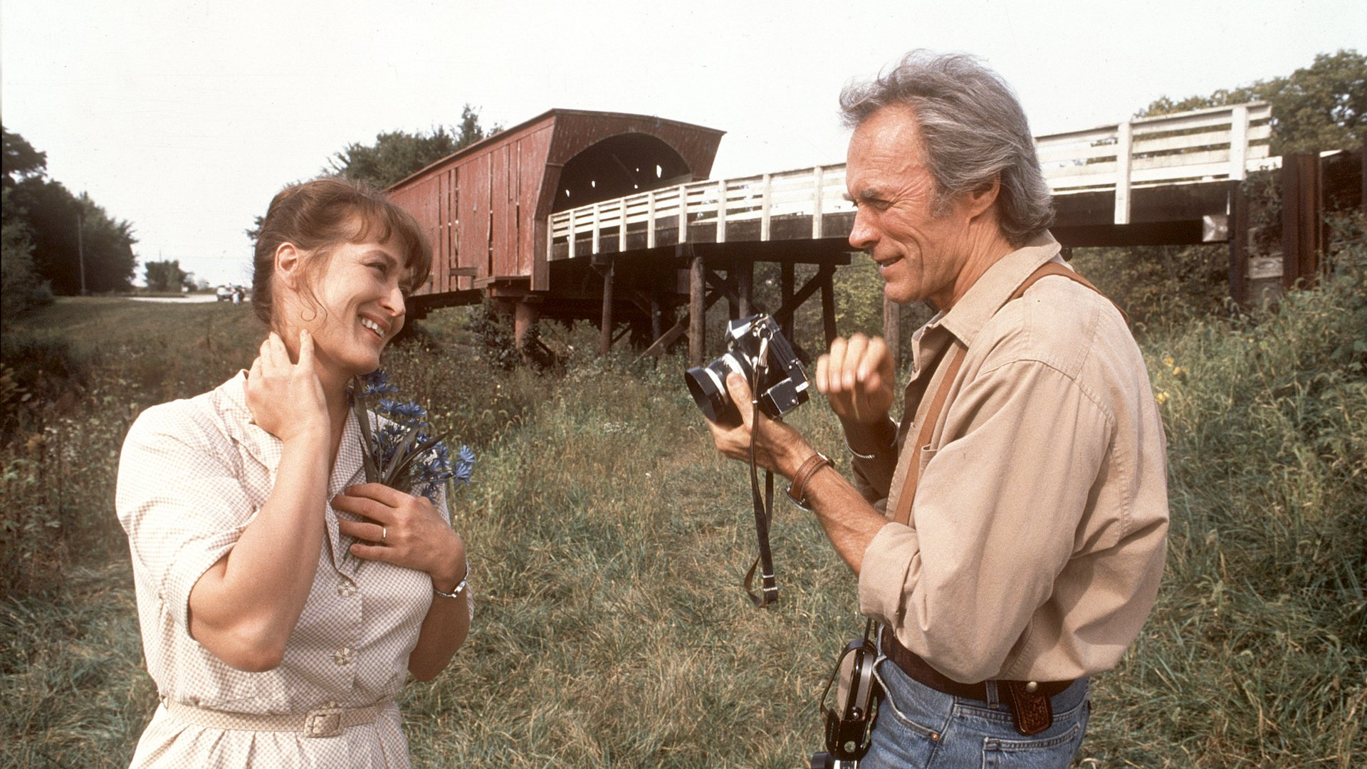 Meryl Streep and Clint Eastwood in Bridges of Madison County. Streep poses with flowers in front of covered bridge. Eastwood holding a camera, appears to be preparing to take her photo.