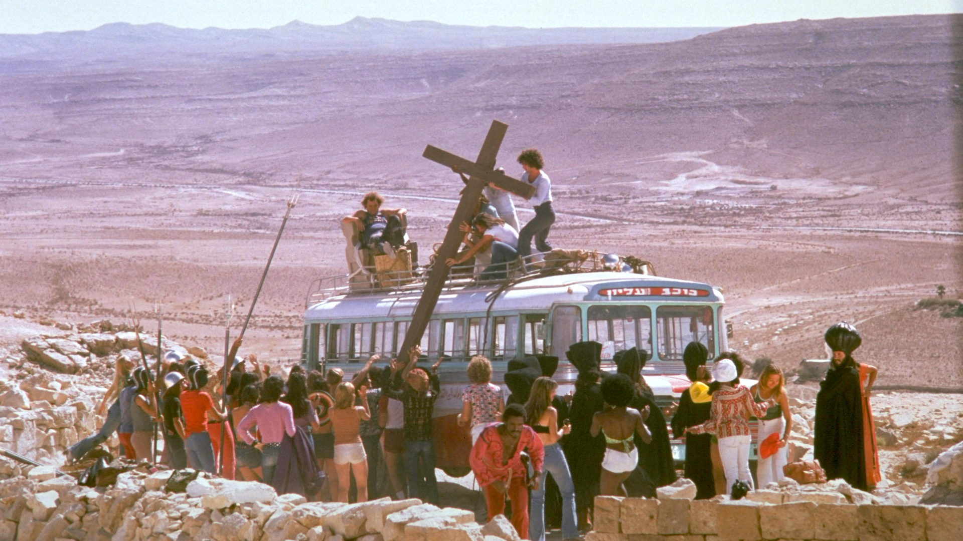 Desert scene from Jesus Christ Superstar. A large cross is loaded onto the roof of a bus while a crowd gathers around.