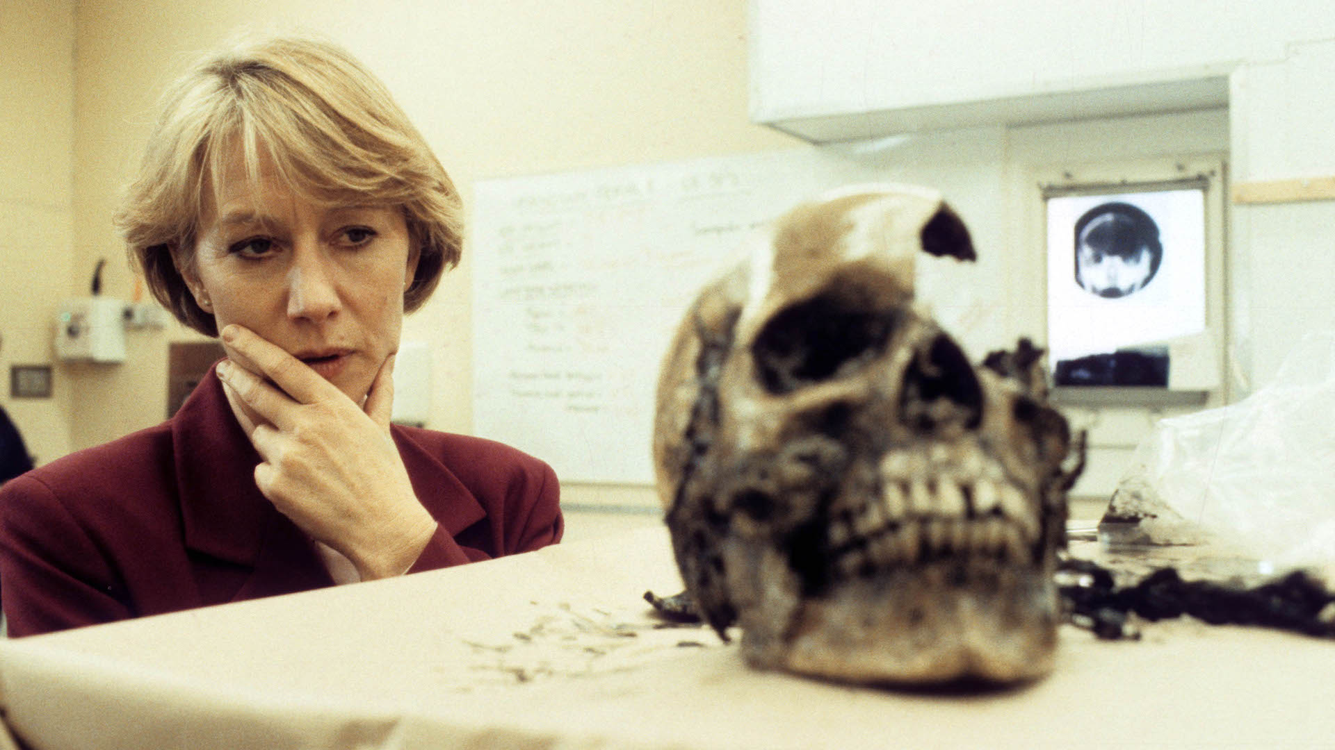 Helen Mirren, as Detective Jane Tennison in Prime Suspect, looks at the skull of a murder victim.