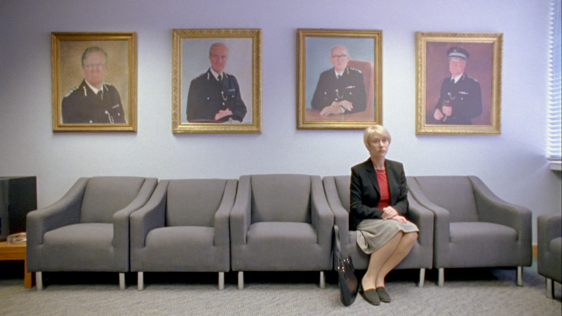 Helen Mirren, as Detective Jane Tennison in Prime Suspect, sits alone in a waiting room. Above her hang the portraits of four male police officials.