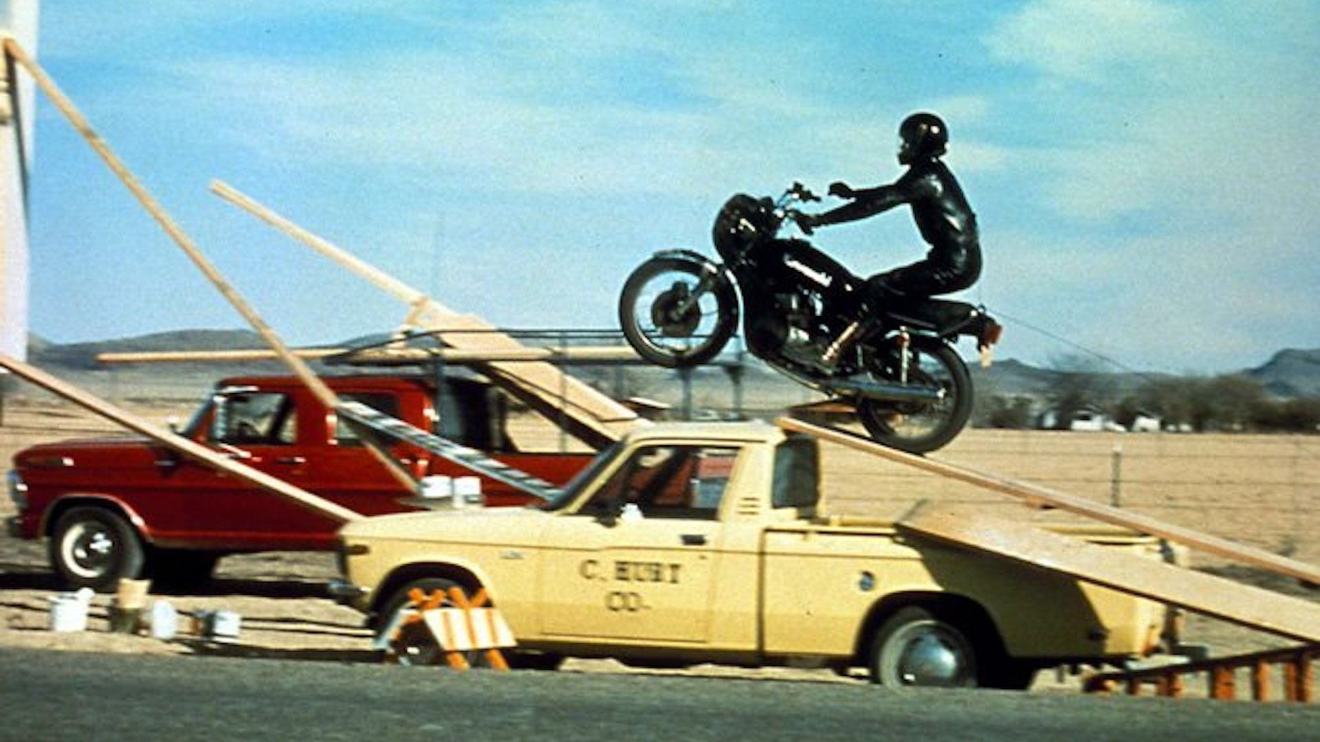 A motorcyclist completes a jump stunt over a truck in The Gumball Rally