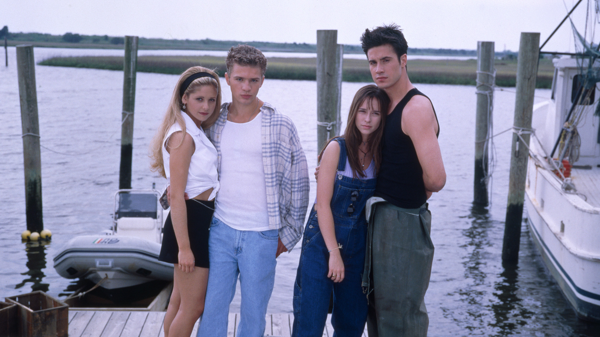 Sarah Michelle Geller, Jennifer Love Hewitt, Freddie Prinze Jr. and Ryan Philippe stand on a dock in I Know What You Did Last Summer