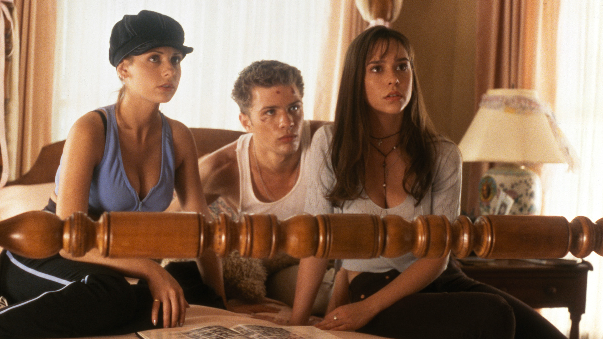 Sarah Michelle Geller, Jennifer Love Hewitt and Ryan Philippe sit on a bed in I Know What You Did Last Summer