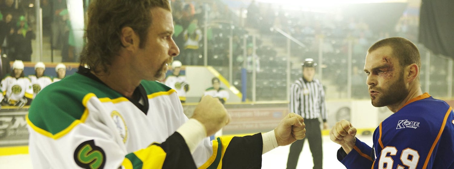 Sean William Scott and Liev Schreiber face off with fists raised in a hockey fight in the film Goon
