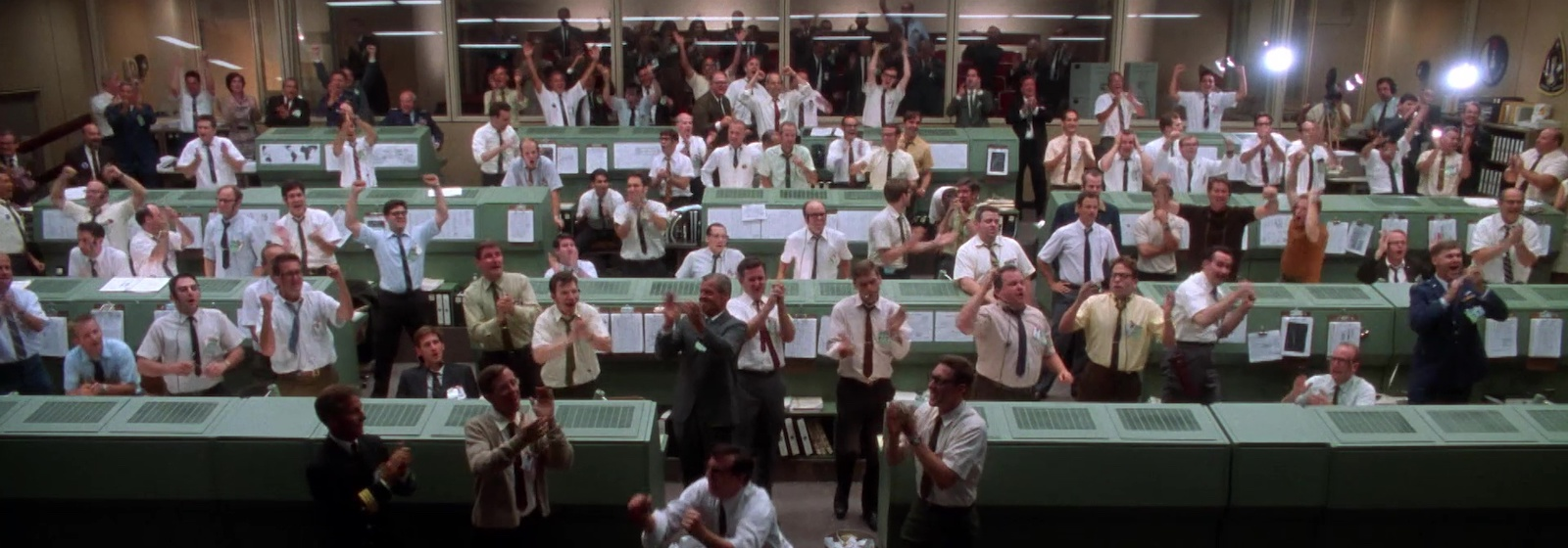 a large control room with many people clapping