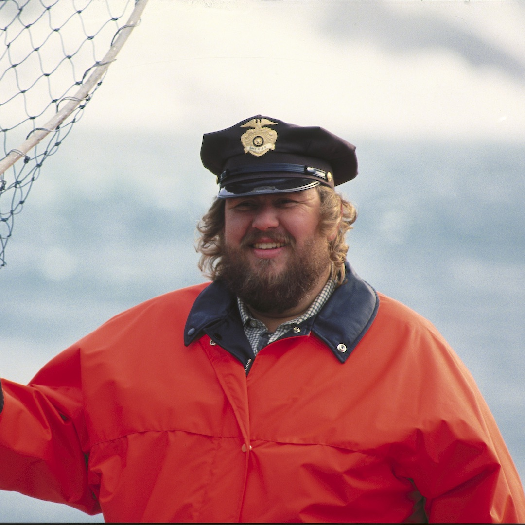 A smiling, bearded John Candy holds a large net as Sheriff Bud Boomer in Canadian Bacon