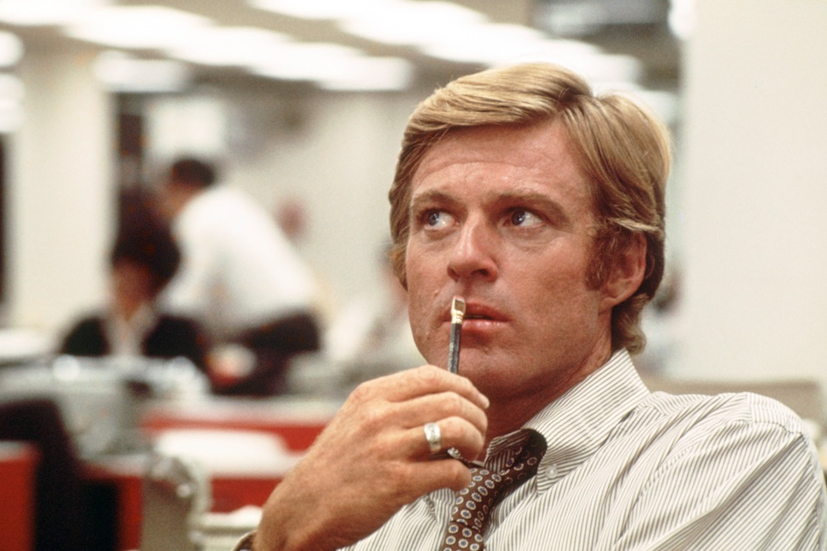 Robert Redford as Bob Woodward sits at a desk in All the President's Men