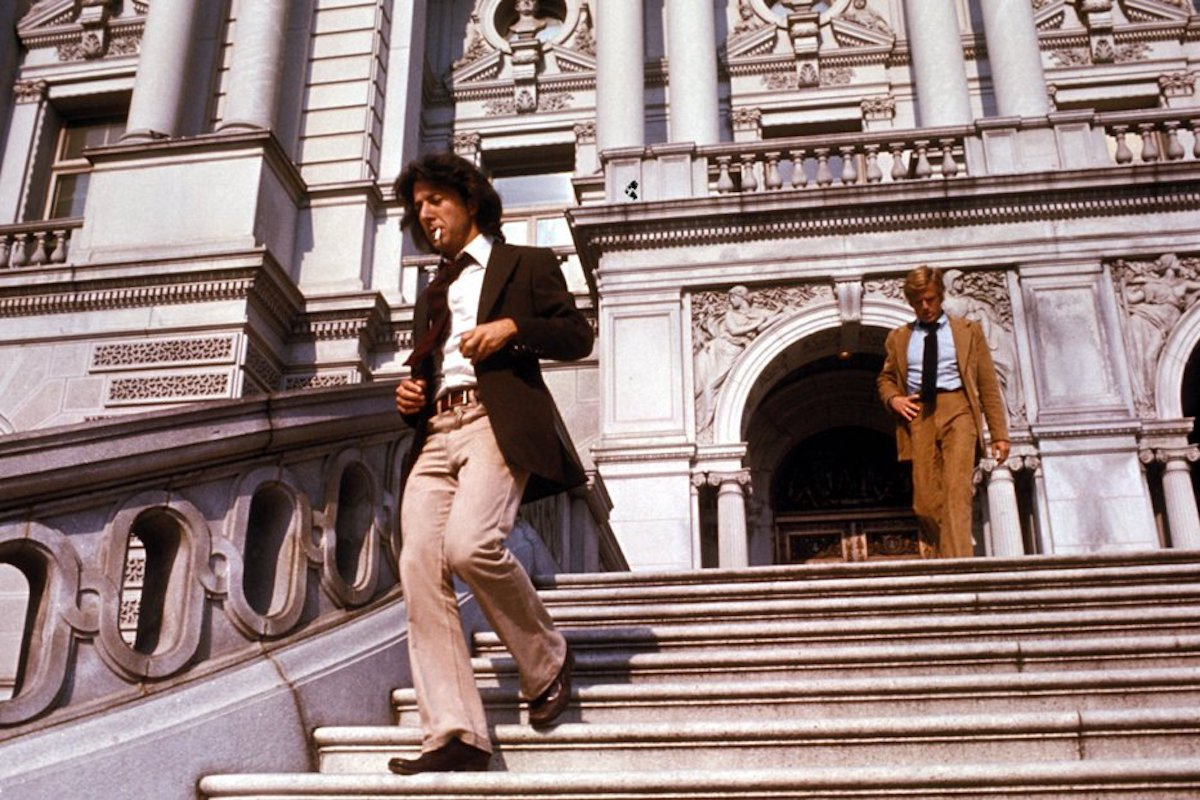 Robert Redford as Bob Woodward and Dustin Hoffman as Carl Bernstein descend the stairs in front of an ornate building in All the President's Men