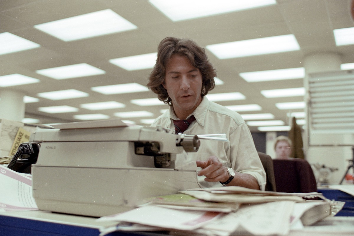 Dustin Hoffman as Carl Bernstein sits at a typewriter in All the President's Men