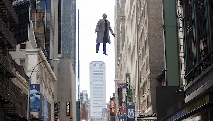 Michael Keaton wearing a trench coat floats high above a New York street in Birdman
