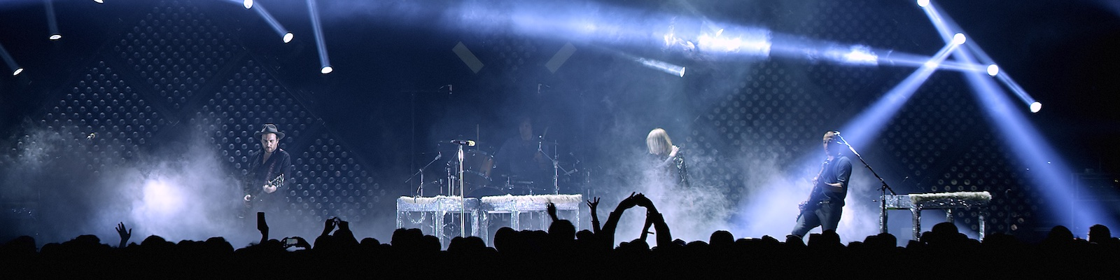 spotlights cross a stage as the rock band Metric performs in front of an audience