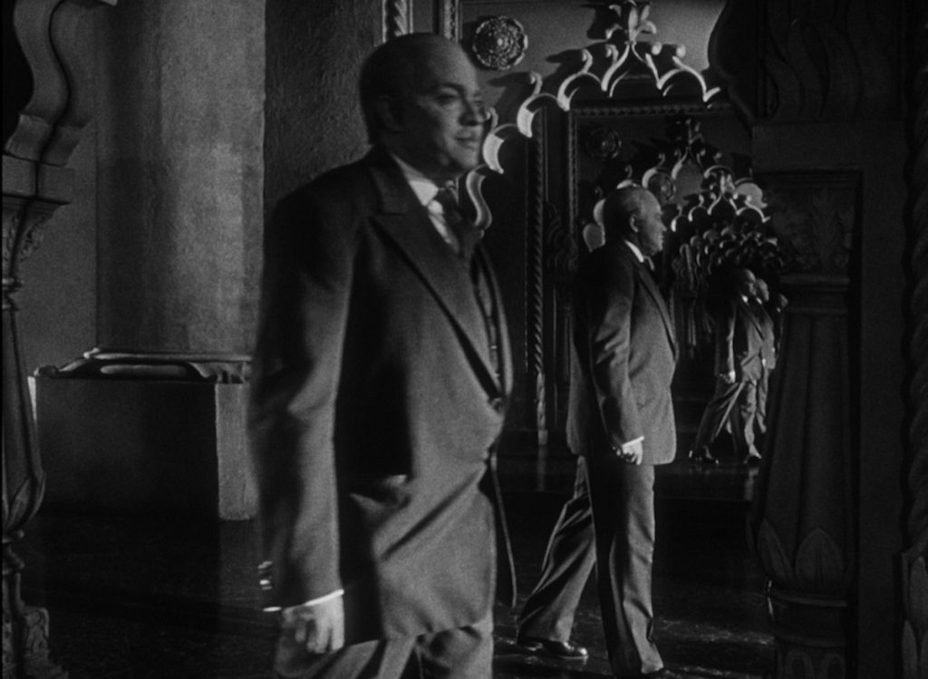 As Orson Welles as Charles Foster Kane walks through a room, his image is reflected endlessly in two mirrors facing eachother