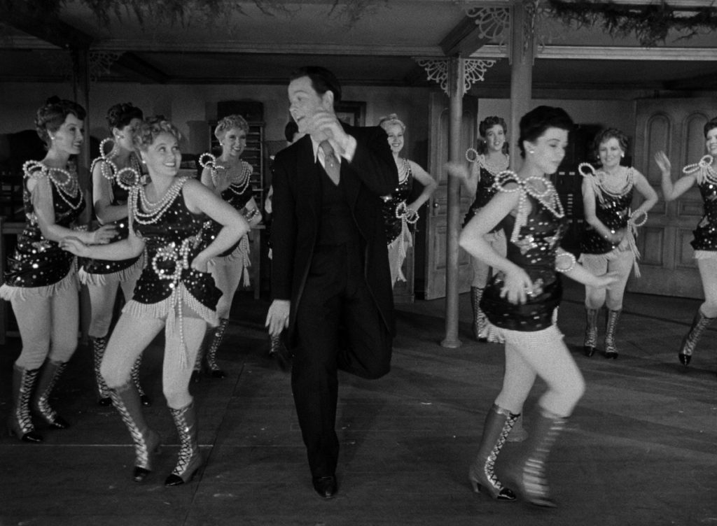 Orson Welles as Charles Foster Kane in a business suit dances with a troupe of chorus girls in sequin and pearl dresses