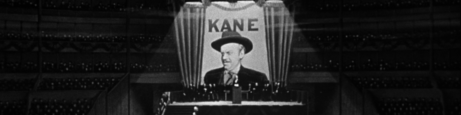 Orson Welles as Charles Foster Kane stands on stage in front of a large poster bearing his image and the word KANE