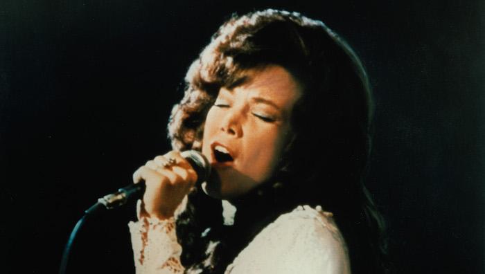 Sissy Spacek as Loretta Lynn sings into a microphone in Coal Miner's Daughter (1980)