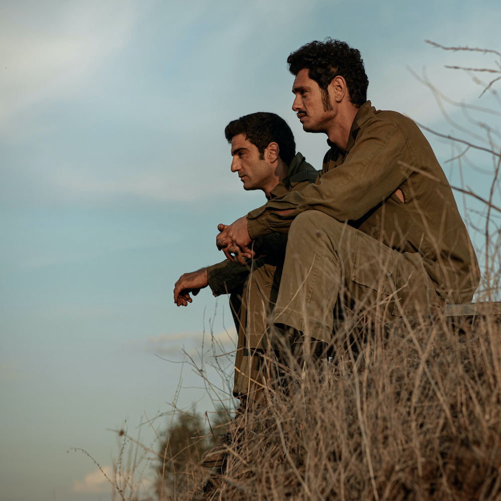 Two men in army uniforms sit on a grassy hill in Valley of Tears