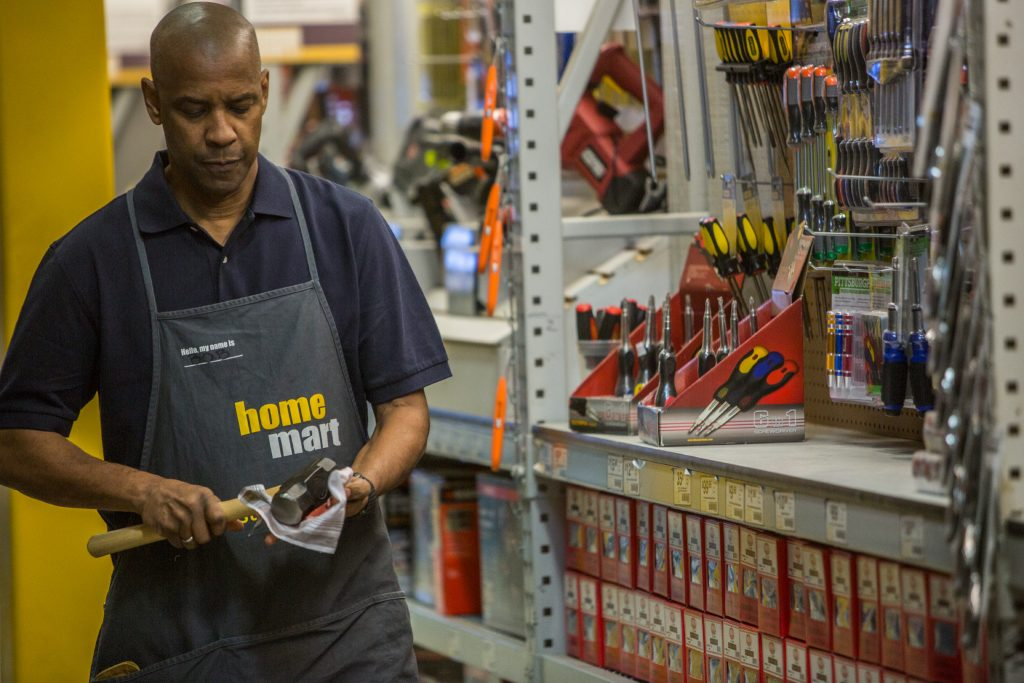 Denzel Washington stands in a hardware store holding a hammer