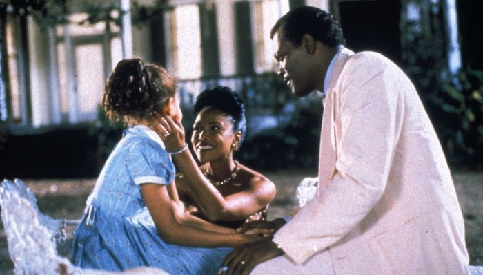 Jurnee Smollett wearing a prim dress sits outside a stately home on an ornate white painted iron bench. Samuel L Jackson in a white suit sits across from her holding her hand, and Lynn Whitfield wearing a strapless evening gown kneels while caressing Jurnee's face.