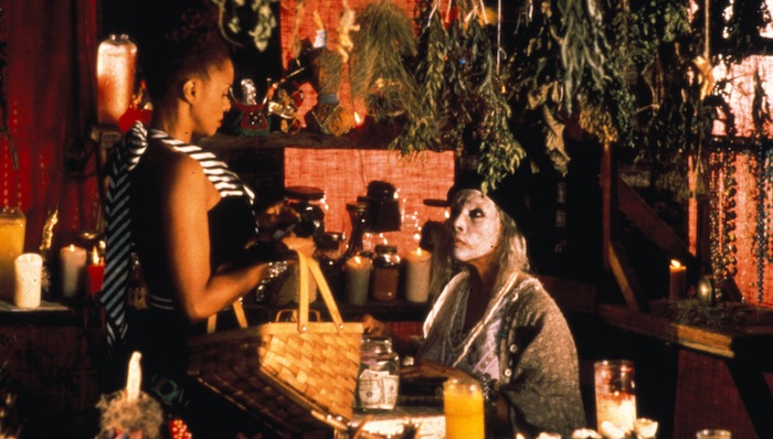 Surrounded by many lit candles in a room with herbs hanging from the ceiling, Debbi Morgan carries a basket and stands before a seated Diahann Carroll, whose face is painted white.