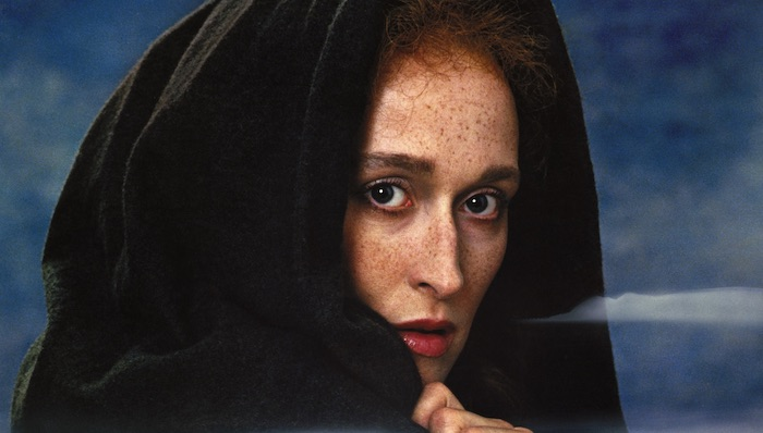 Meryl Streep wears a hooded cape and looks into the camera dramatically in the poster art for The French Lieutenant's Woman