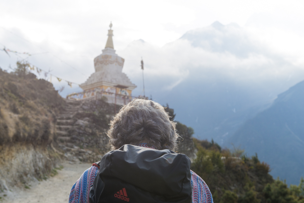 (from behind) a person climbs to a holy site with a mountain looming in the distance