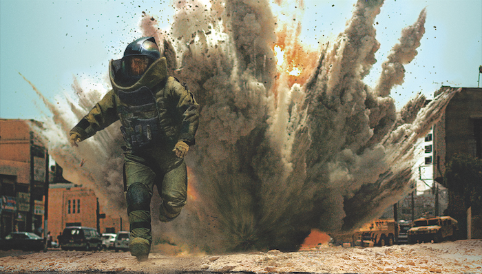 A bomb squad technician in protective gear runs from an explosion in The Hurt Locker