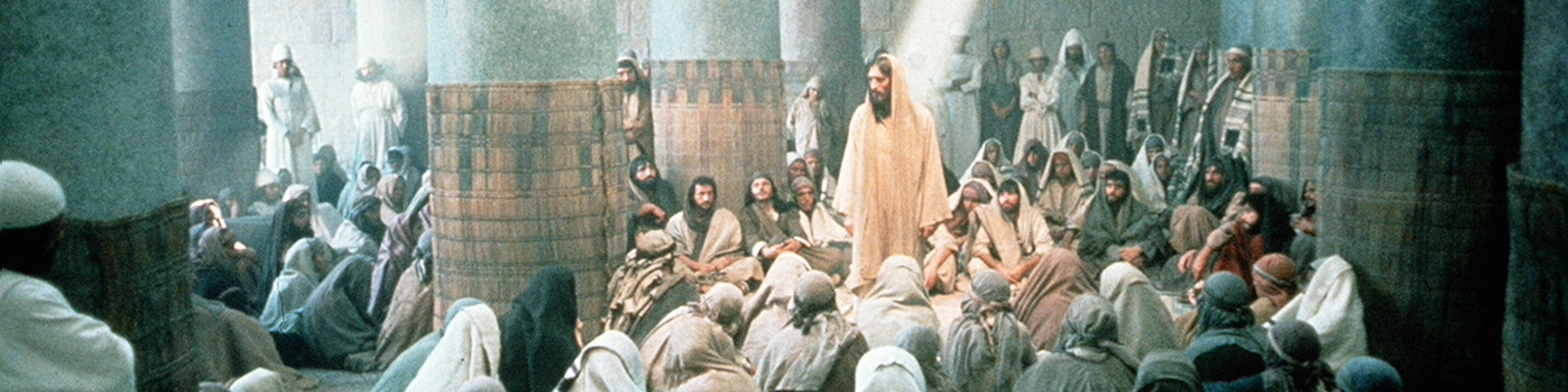 JESUS (ROBERT POWELL) PREACHES TO HIS MANY FOLLOWERS IN WHAT LOOKS LIKE A TEMPLE, A BEAM OF LIGHT FOCUSES ON JESUS THROUGH A WINDOW