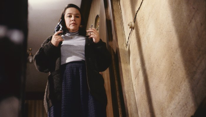 Kathy Bates as deranged fan Annie Wilkes holds a gun and a syringe in Misery