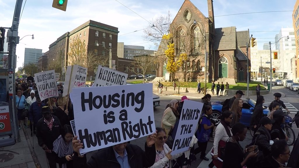 "Protesters march on a street in front of a church. The hold signs reading ""Housing is a Human Right"" and ""What's the plan?"""