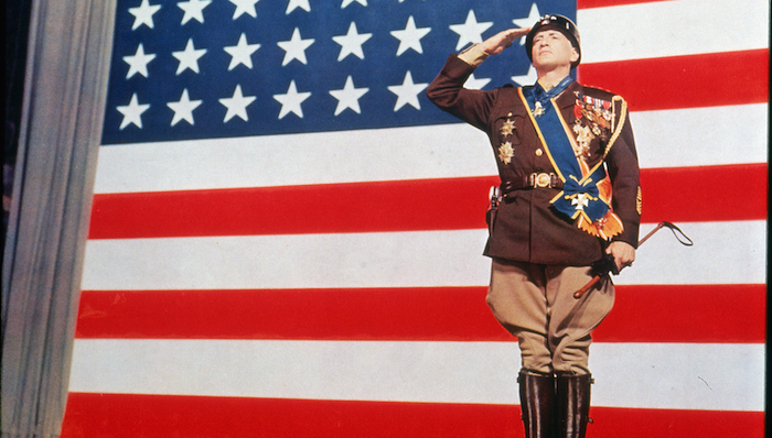 George C. Scott as General Patton stands in salute in front of a large American flag