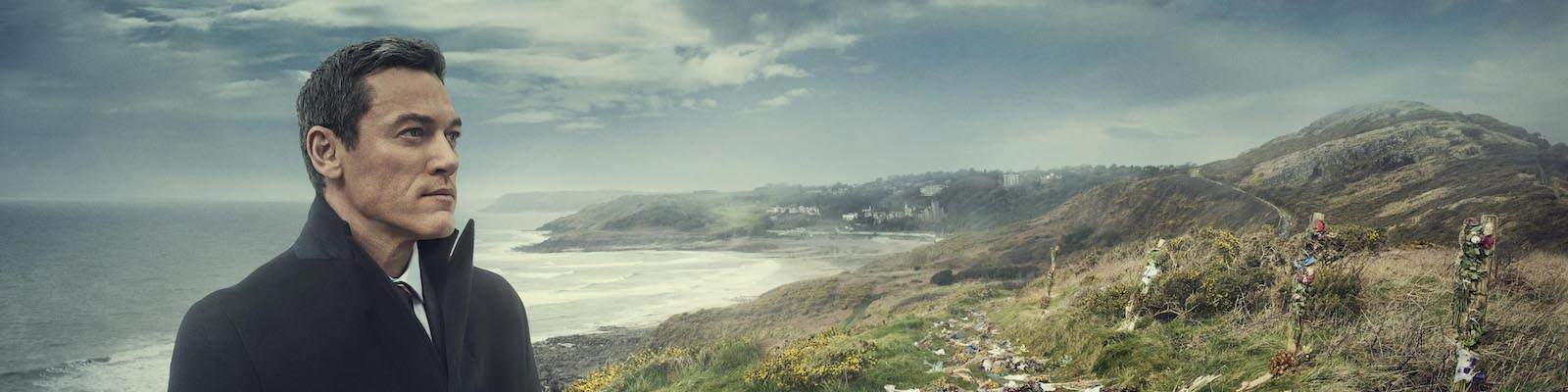 Actor Luke Evans stands near a makeshift memorial of bouquets of flowers on a windswept hill above a beach