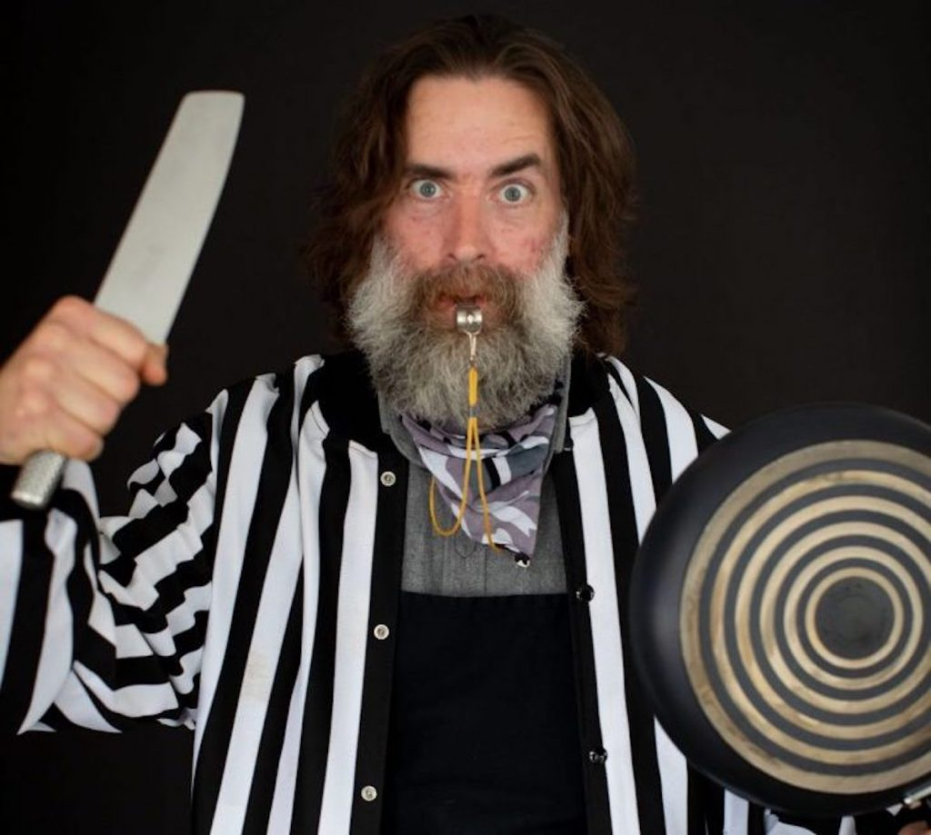 Sam Higgs poses for a portrait wielding a cooking knife and a frying pan.