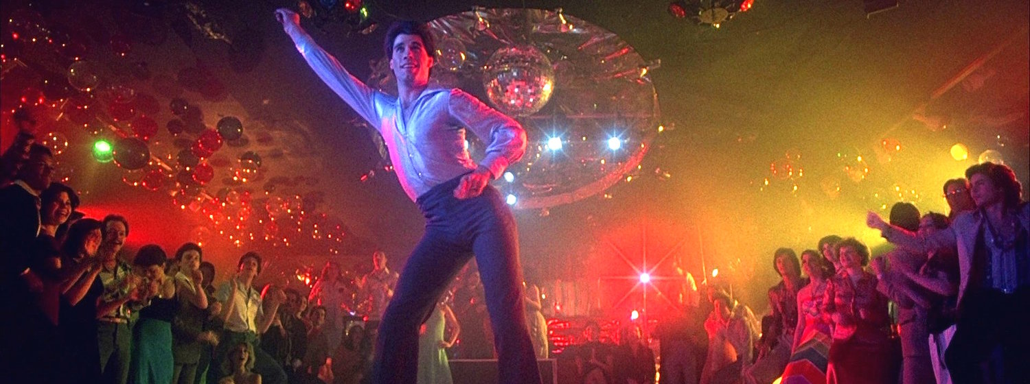 John Travolta poses in a disco move on a dance floor in Saturday Night Fever