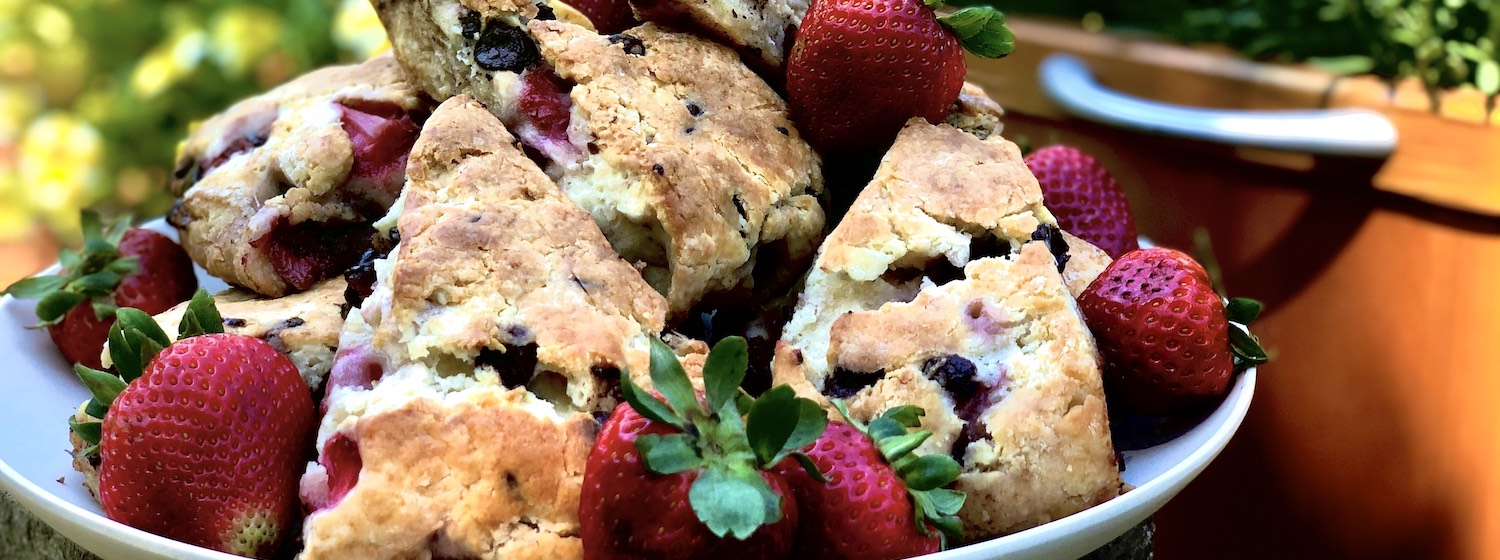 A plate of strawberry and chocolate chip scones served with fresh strawberries