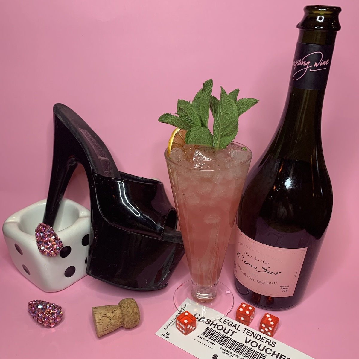 """Pink """"You Don't Nomi"""" Showgirls-Inspired cocktail in a tall glass with mint and citrus"""