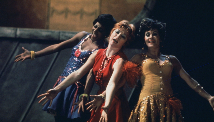Shirley MacLaine sings with the cast of Sweet Charity, all dressed in bright primary colour dresses