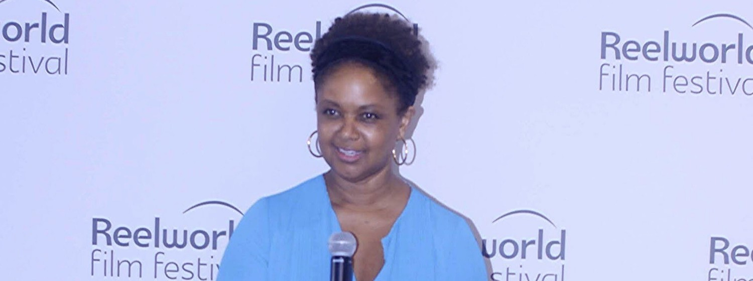 Reelworld founder Tonya Williams holding a microphone in front of a backdrop featuring the Reelworld logo
