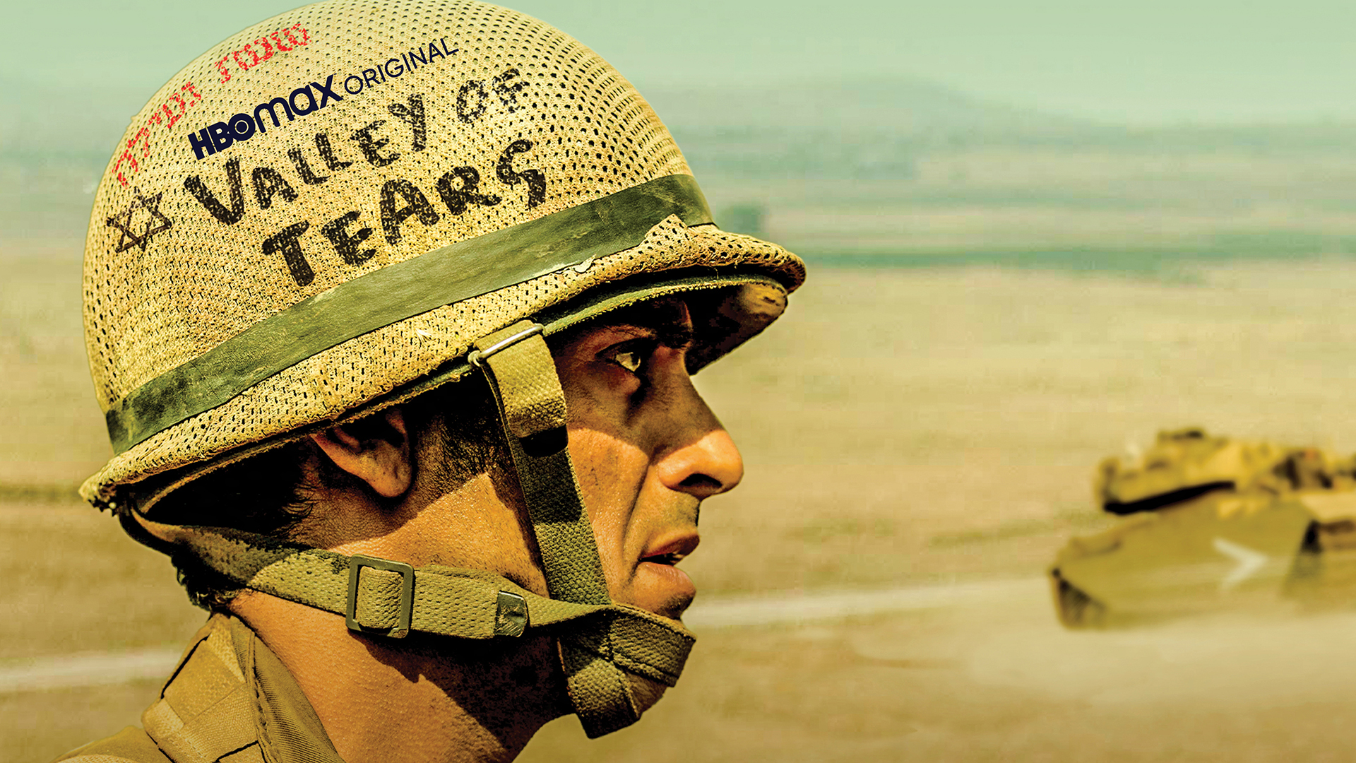 "A man stands in a desert, a tank in the distance. On his helmet is the logo for the series ""Valley of Tears"""