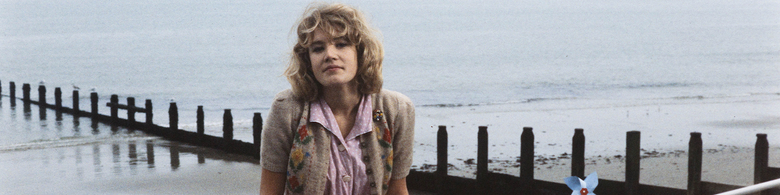 Emily Lloyd sits on a railing with the sea in the background