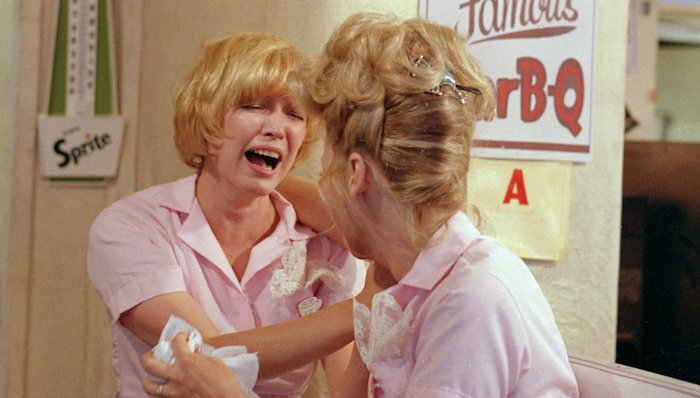 A sobbing Ellen Burstyn is consoled by a dinner coworker, both wearing pink waitress uniforms, in Alice Doesn't Live Here Anymore