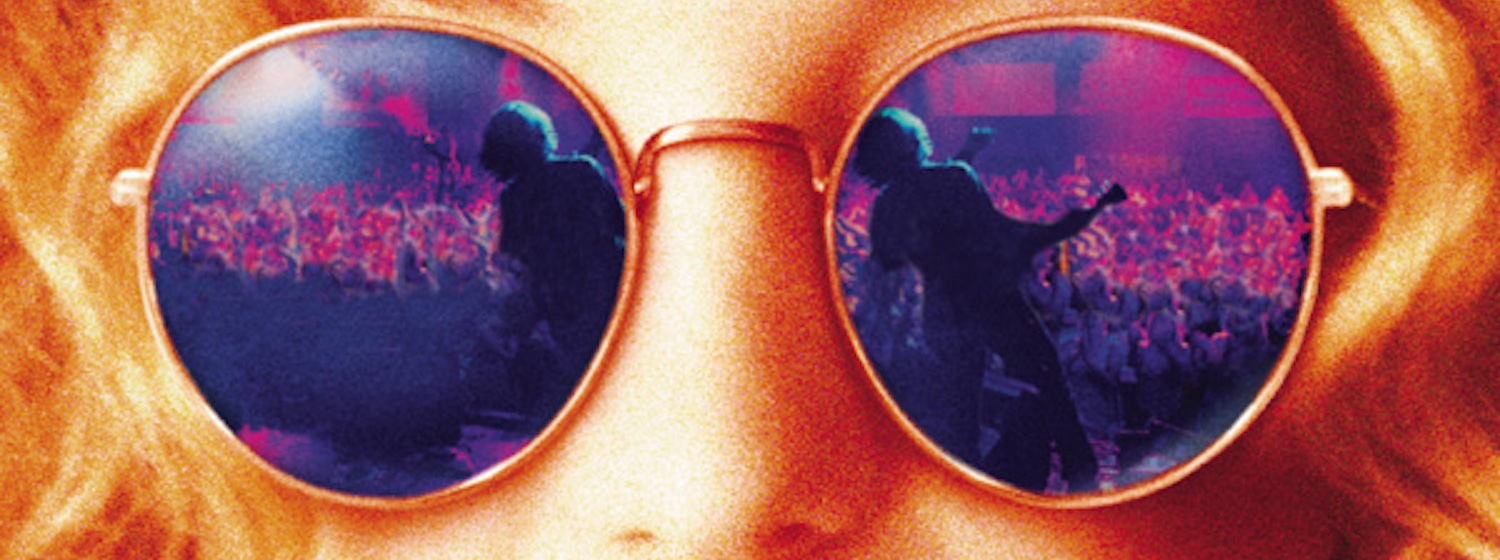 close up of kate hudson wearing mirrored sunglasses reflecting a band playing on a stage from the poster art for Almost Famous