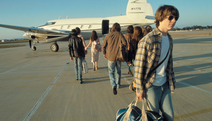 Patrick Fugit walks away from a small propeller plane while a band and it's entourage boards in Almost Famous