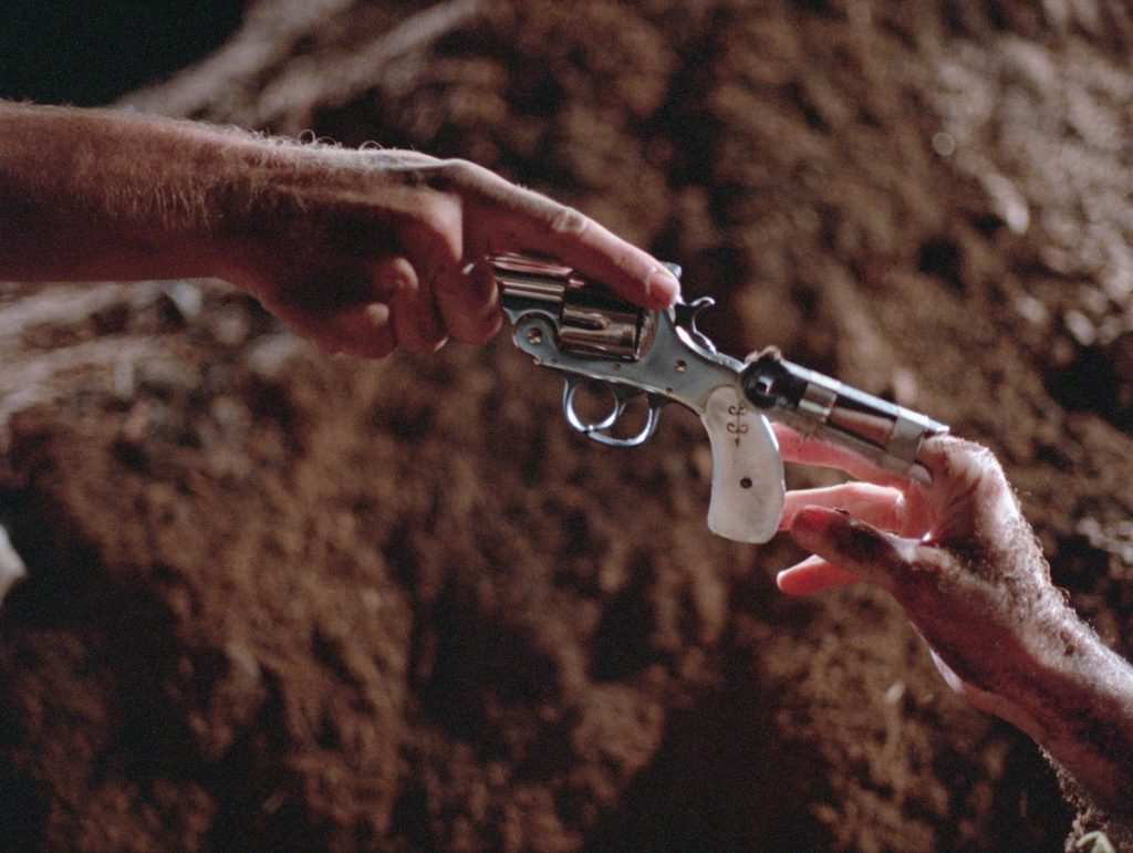 """in a dirt field, a close up of a pistol being passed between two hands in reference to Michaelangelo's """"The Creation of Adam"""" fresco in the Sistine Chapel"""