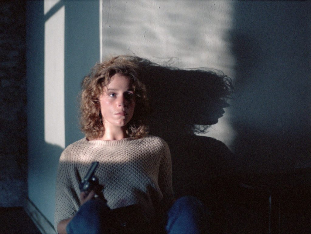 Looking apprehensive, Frances Mcdormand sits leaning against a wall holding a pistol