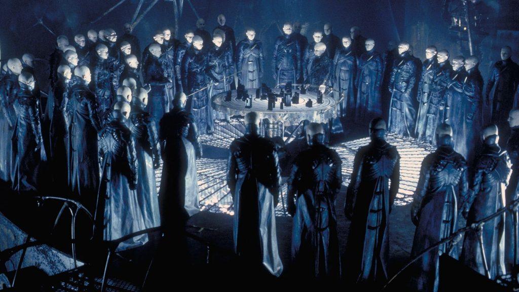"Alien ""Strangers"" gather around a circular table in Dark City"