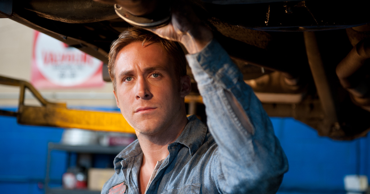 Ryan Gosling stands under a car that has been raised in a garage in Drive