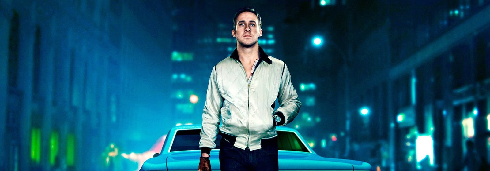 Ryan Gosling stands behind a car on a blue-lit city street in Drive