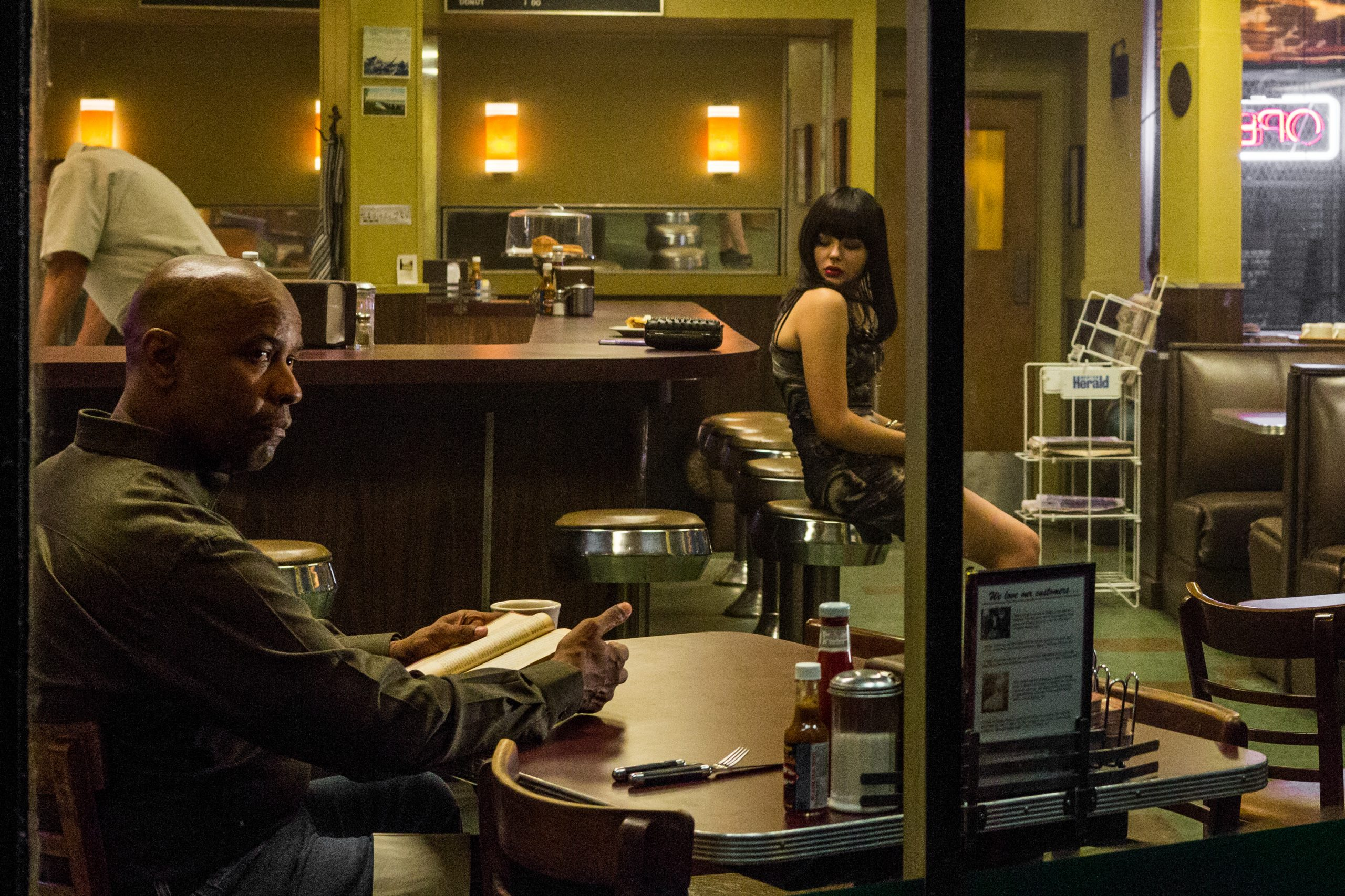 Denzel Washington sits at a diner table with a book while Chloe Grace Moretz sits on a stool at the counter